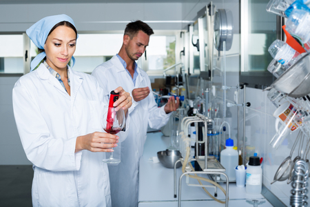 Young woman  expert in white coat  filtration of wine in chemistry Stock Photo