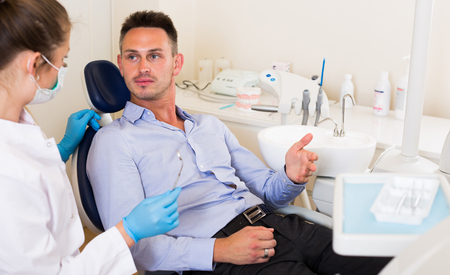 Adult man is consulting with dentist in the hospital.