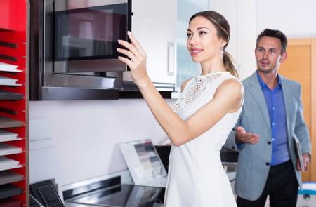 Pareja está eligiendo nuevo microondas en la tienda de muebles de cocina.