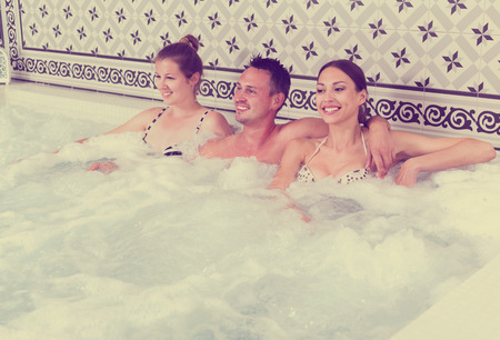 Company of three people relaxing enjoying jacuzzi hot tub bubble bath in spa complex