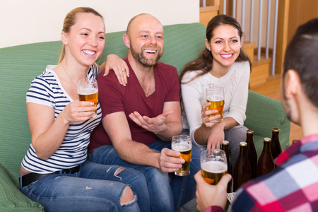 Happy adults drinking beer and laughing at home Stock Photo
