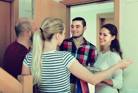 Positieve glimlachende gasten met cadeaus en cake die in de deuropening staan. Focus op meisje