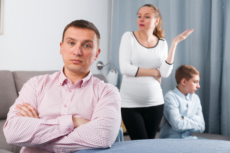 Pregnant mother and son having disagreement with father at home