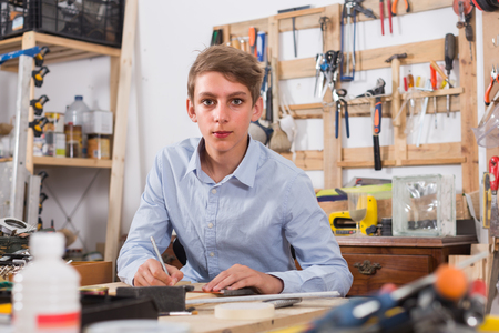 toolroom: Handsome english teenager  smiling and working with wood in the workshop Stock Photo