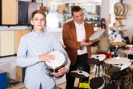 happy american teenager and father deciding on drum unit in musical shop