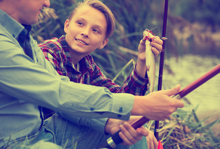 Portrait of father with teenager son having fish in hands outdoors