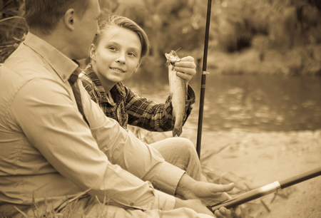 Portrait of laughing father with teenager son having fish in hands outdoors