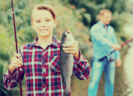 gudgeon: Portrait of laughing teenager boy having fish in hands outdoors