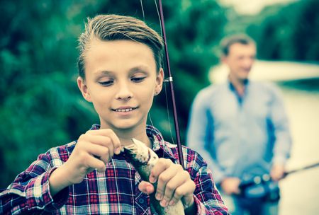 gudgeon: Glad teenager boy holding and looking at fish on a hook