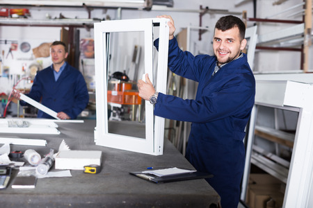 Cheerful labour demonstrating finished PVC profiles and windows at factory