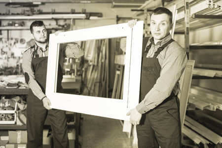 Adult workman showing PVC manufacturing output in workshop
