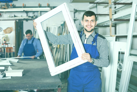 Laborer is demonstrating the window frame in workshop. Stock Photo