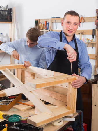 toolroom: happy british teacher and boy chiselling a wooden bench in  workshop