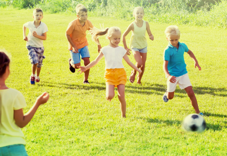Happy cheerful children playing football on meadow at sunny day. Selective focus