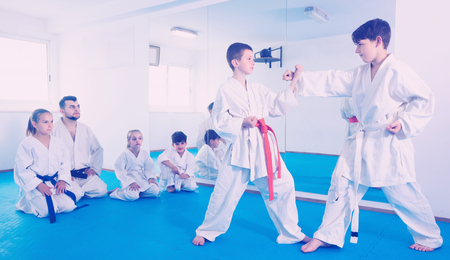 Friendly smiling boys training in pair to use karate technique during class