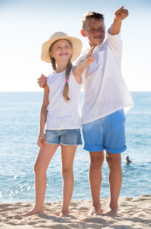niños platicando: portrait of smiling boy and girl pointing with finger on sandy beach on bright weather Foto de archivo