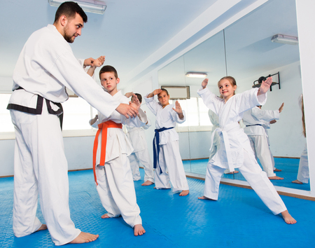Trainer is correcting children moves in karate class.