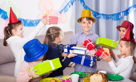 animated boy: Smiling european  children giving presents to little boy during party Stock Photo