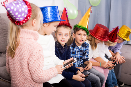 Smiling children playing with their smartphones together at party