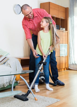 Smiling adult man teaching little daughter vacuuming during clean-up at home