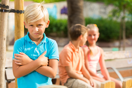 argue kid: Portrait of offended boy which is standing outside of the company in the park.