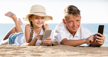 Portrait of two beautiful children in elementary school age on beach with phone in hands