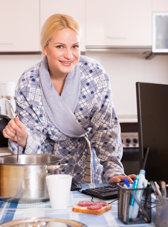 Happy woman with dishware working on PC at kitchen