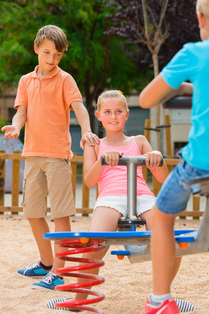 Cheerful children are teetering on the swing on the playground. Stock Photo