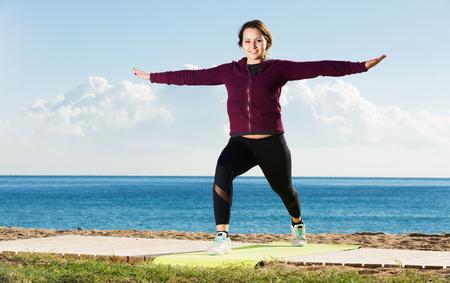 Portrait of cheerful young woman doing yoga asanas and pranayama at seaside