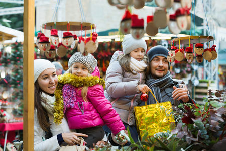 Smiling cheerful family of four buying Caga Tio at Christmas market. Focus on woman