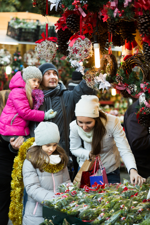 Young family of four choosing floral decorations at market. Focus on brunette girl