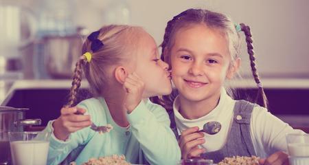 Portrait of smiling cute little sisters eating porridge in kitchen