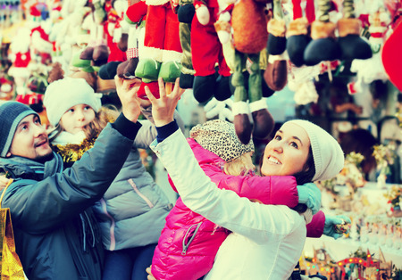Family with children purchasing a Christmas decoration and souvenirs at the fair. Focus on women