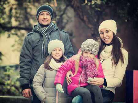 Winter portrait of cheerful smiling adults with little daughters . Focus on woman and ittle girl