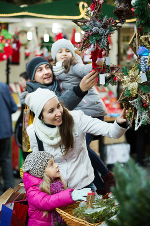 Young happy family of four choosing floral decorations at market. Focus on blonde girl and woman