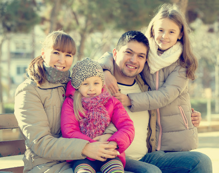 positive family with two girls outdoors in sunny fall day