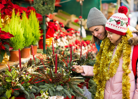overspending: Glad mom with girl looking at flowers decoration at Christmas market Stock Photo