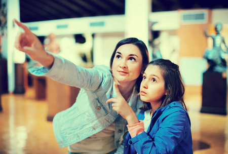 Young positive mother and daughter enjoying expositions of previous centuries in museum