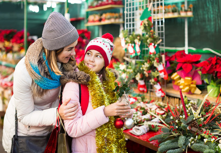 overspending: positive woman with daughter looking at floral decoration at Cristmas fair