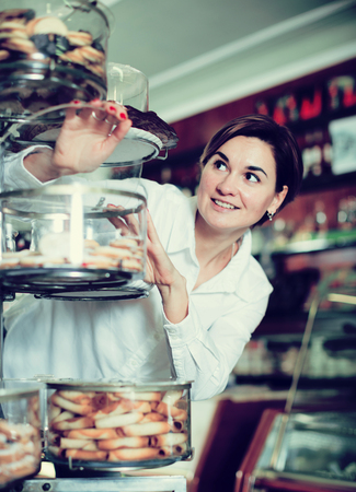 sorts: Young female client choosing delicious dessert in confectionery Stock Photo