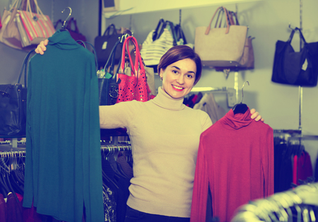 pullovers: Young happy cheerful female shopper examining turtleneck sweaters in women's cloths shop