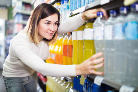 sorts: Girl customer looking for the refreshing beverages at supermarket