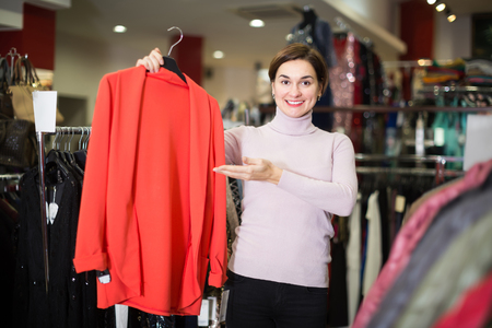 Female customer deciding on jersey cardigan in women's cloths shop