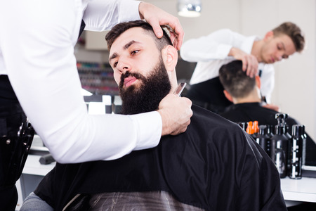 barbershop: Glad man hairdresser forming beard of client into new shape at hair salon