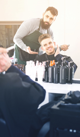 Young spanish male hairdresser showing resulting haircut to client at hair salon