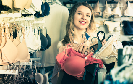 Female is enjoying her purchases in underwear shop.