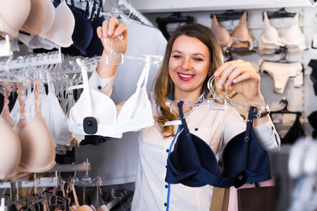 Smiling woman shopper examining bras in underwear shop Stock Photo