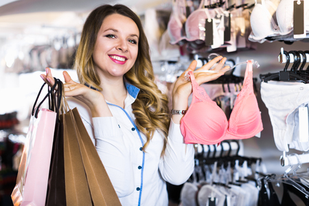 Smiling female shopper is enjoying her purchases in underwear shop. Stock Photo