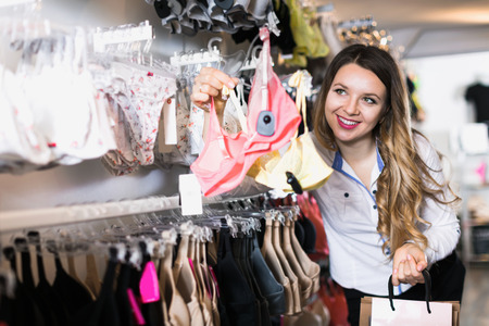 Young woman shopper examining clothing in underwear shop