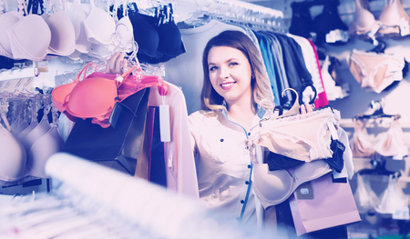 Happy cheerful  female shopper boasting her purchases in underwear shop